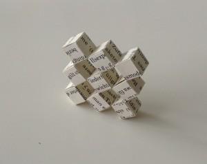 Ein beweglicher Würfel, der aus einem alten Buch geschnitten wurde. Die Buchseite wird zerschnitten und die Streifen werden in Origami-Manier gefaltet.