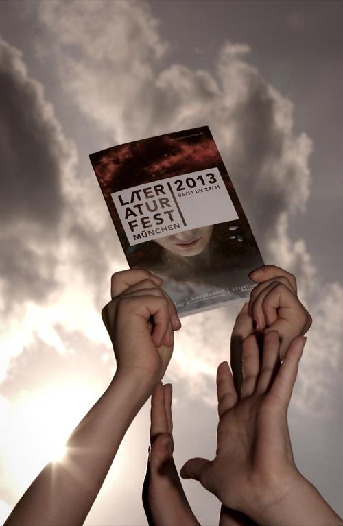 Hände halten Broschüre für Literaturfest München 2013 in die Höhe